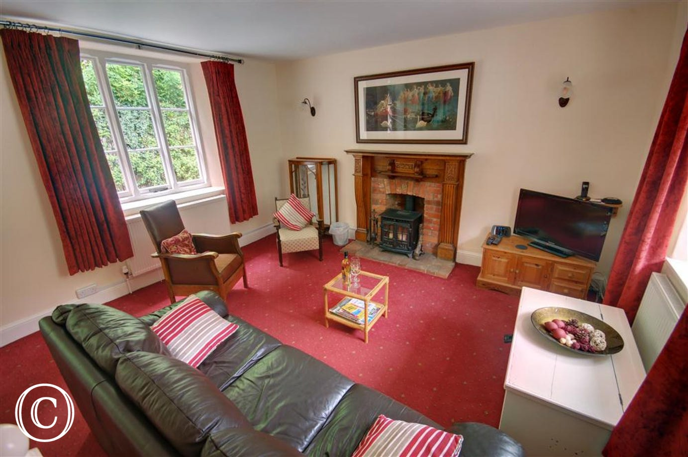 Spacious sitting room with log burner in feature fireplace