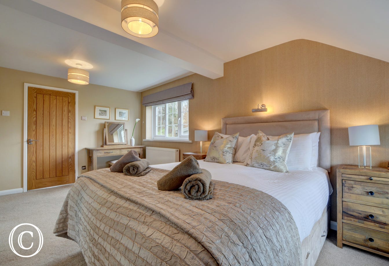 The luxurious master bedroom with ensuite bathroom and countryside views