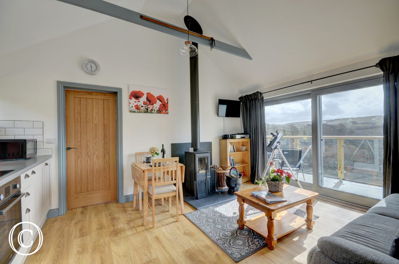 The open plan living space has a vaulted ceiling, woodburning stove and a dining area