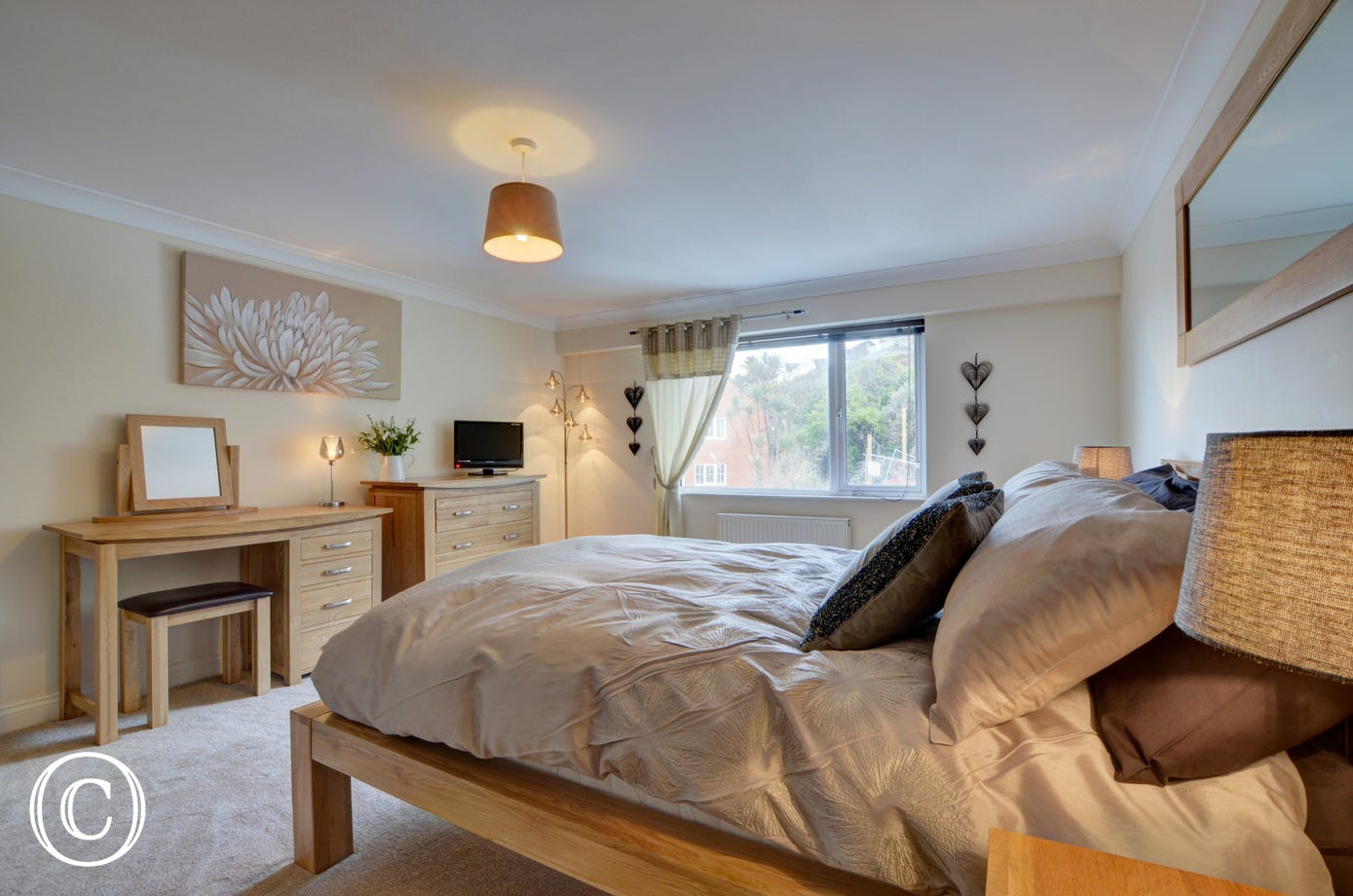The stylish master bedroom with double bed and TV