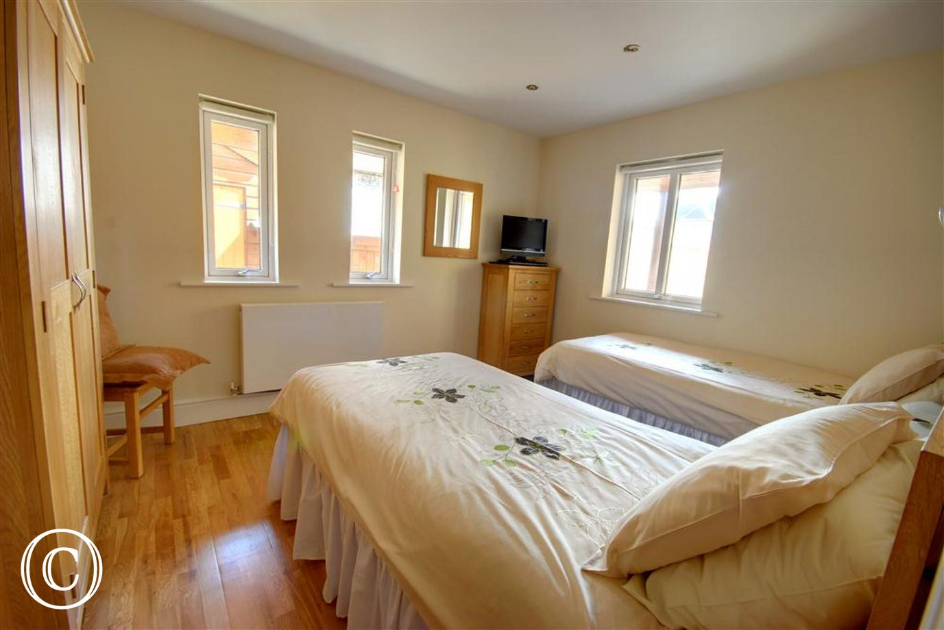 Simply decorated twin bedroom with oak flooring and matching furniture.