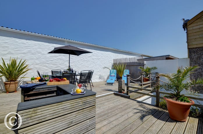 The rear outdoor area is surrounded by whitewashed walls, this secluded, raised and decked space makes a great sun trap