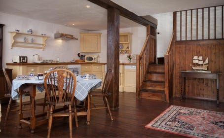 country cottage with exposed beams and open-plan kitchen dining room