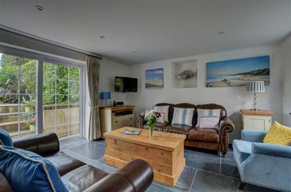 The lovely sitting room overlooks the garden with patio doors leading out onto the patio