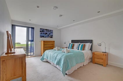 The sumptuous master bedroom is located on the lower ground floor with direct access to the patio and garden