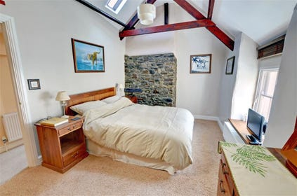 The master bedroom is spacious and has beamed high ceilings and a stone chimney breast
