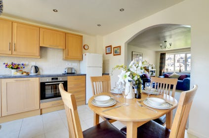 The stylish open plan kitchen and dining area with archway through to the sitting room