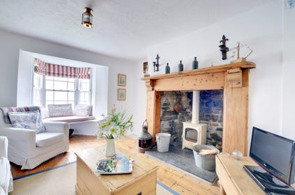 The sitting room has a cosy wood burning stove and an alcoved window seat