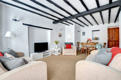 The sitting room has charming character features such as beamed ceilings