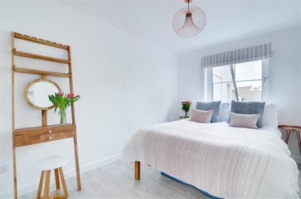 The master bedroom is decorated is calming pastel colours