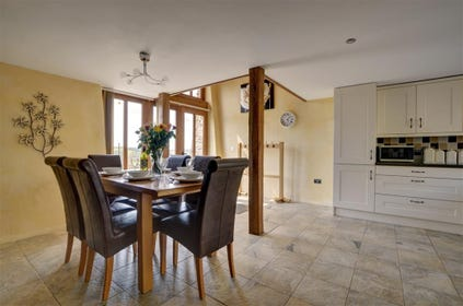 An open plan living/dining/kitchen features floor to ceiling beams and wide expanse of glass doors and windows