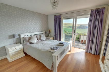 The master bedroom has an ensuite shower room and patio doors out onto the terrace and garden