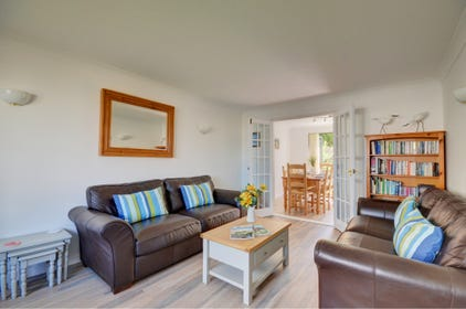 The attractive living room has comfy leather sofas and a door through to the kitchen/breakfast room