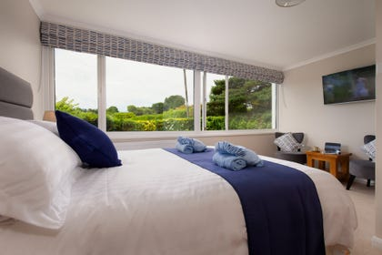 Spacious Master Bedroom with large bright window, bed linen and towels