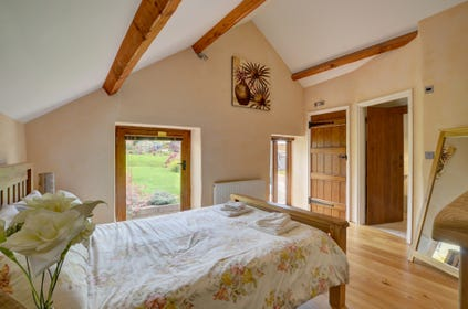 The pretty master bedroom with character beams and an ensuite bathroom