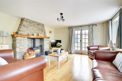The sitting room is a perfect place to relax with comfy leather sofas surrounding a woodburner in a feature stone fireplace