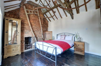 The spacious, characterful double room has a high apex ceiling, cross beams and lights in original barn chandeliers