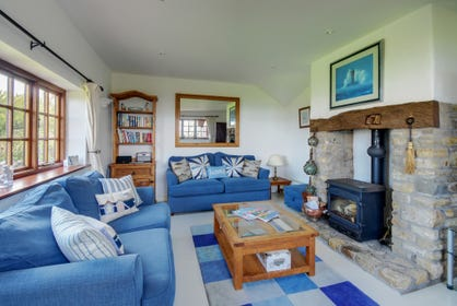 The living room is double aspect with wonderful sea views, character beams and a fireplace with wood burning stove