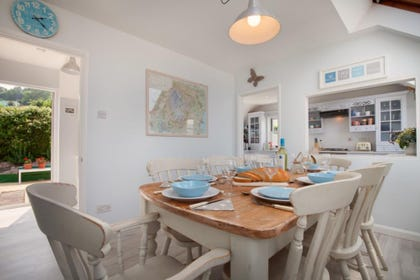 Spacious chic dining area with seating for 8 guests, between kitchen and private garden