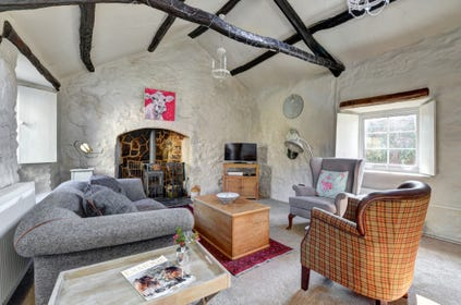 The spacious living room is the heart of the cottage with its high apex ceiling and original cross beams and woodburner