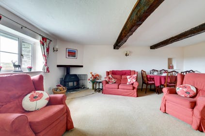 The comfortable living/dining room has lovely views over the garden and  features a wood burning stove, perfect for cosy evenings