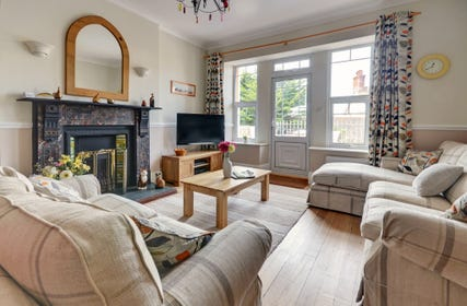 The open plan living/dining area provides a comfortable space with all original oak flooring and original Victorian fireplace