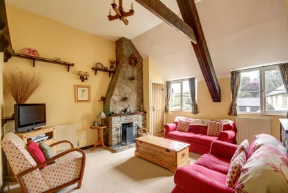 Upstairs the main living area benefits from lovely rural views and cosy sofas surround the open fireplace with exposed beams