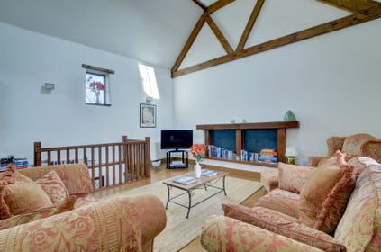 On the ground level there is a spacious and very comfortable living room with vaulted ceiling and feature beams