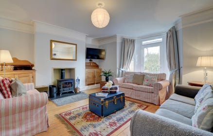 The cosy living area has 3 sofas, a wood burner for the cooler seasons, large wall mounted TV and glazed door to garden area