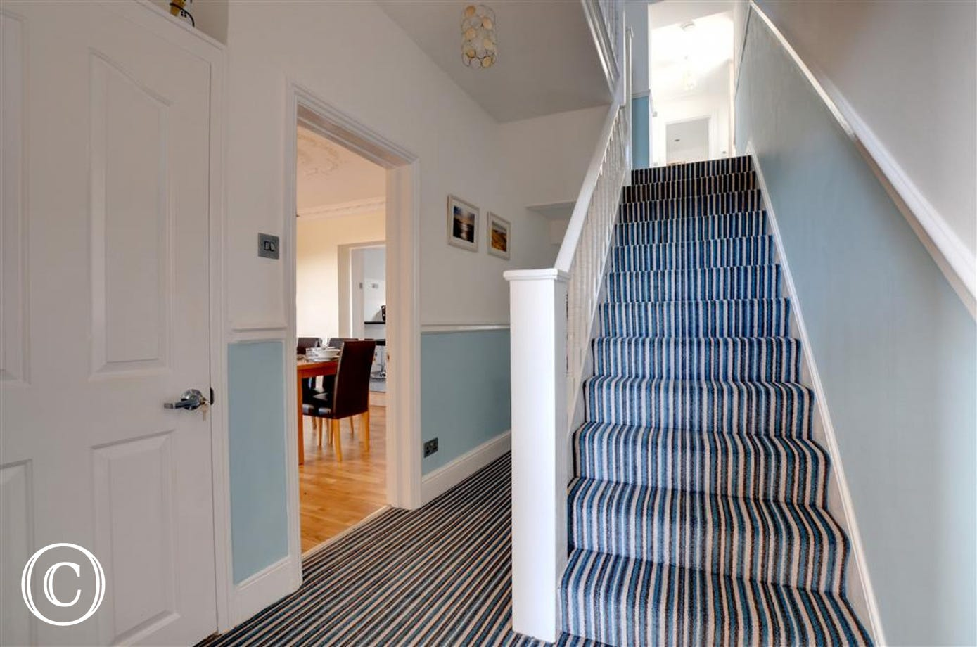 The ground floor entrance has a long hallway with hand built surf board storage and stairs to the first floor
