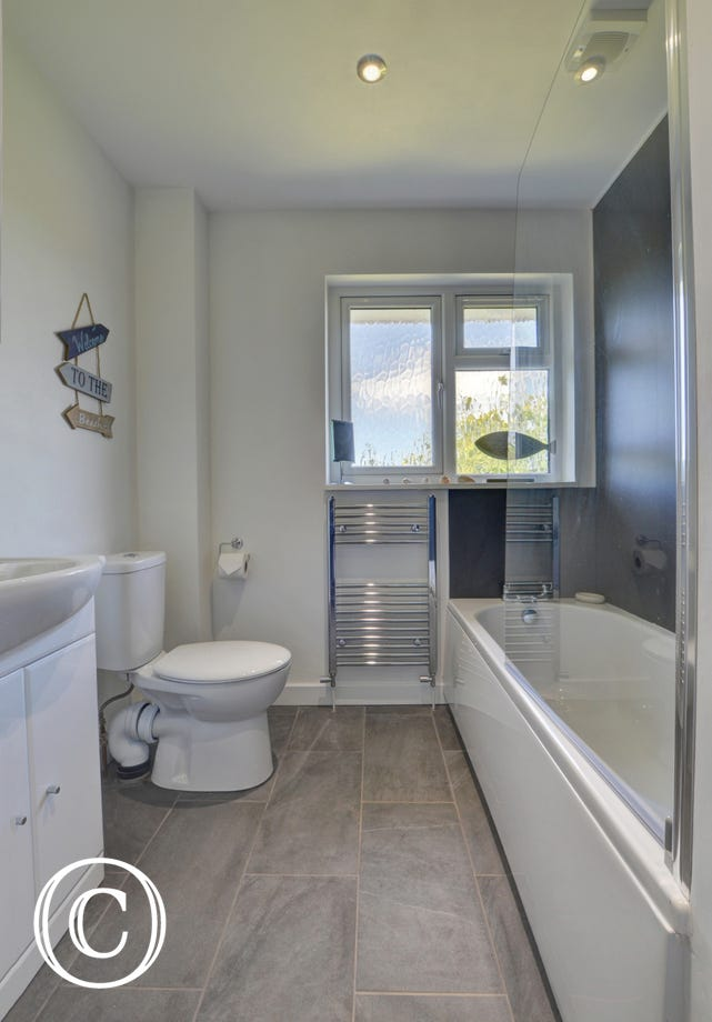 Bathroom with electric shower over bath, WC, basin and heated towel rail