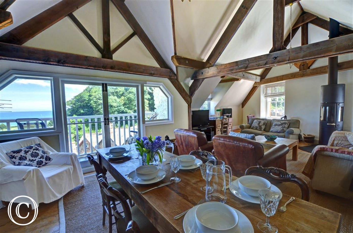 The sitting/dining room has a vaulted ceiling with impressive 'A' frame oak beams.