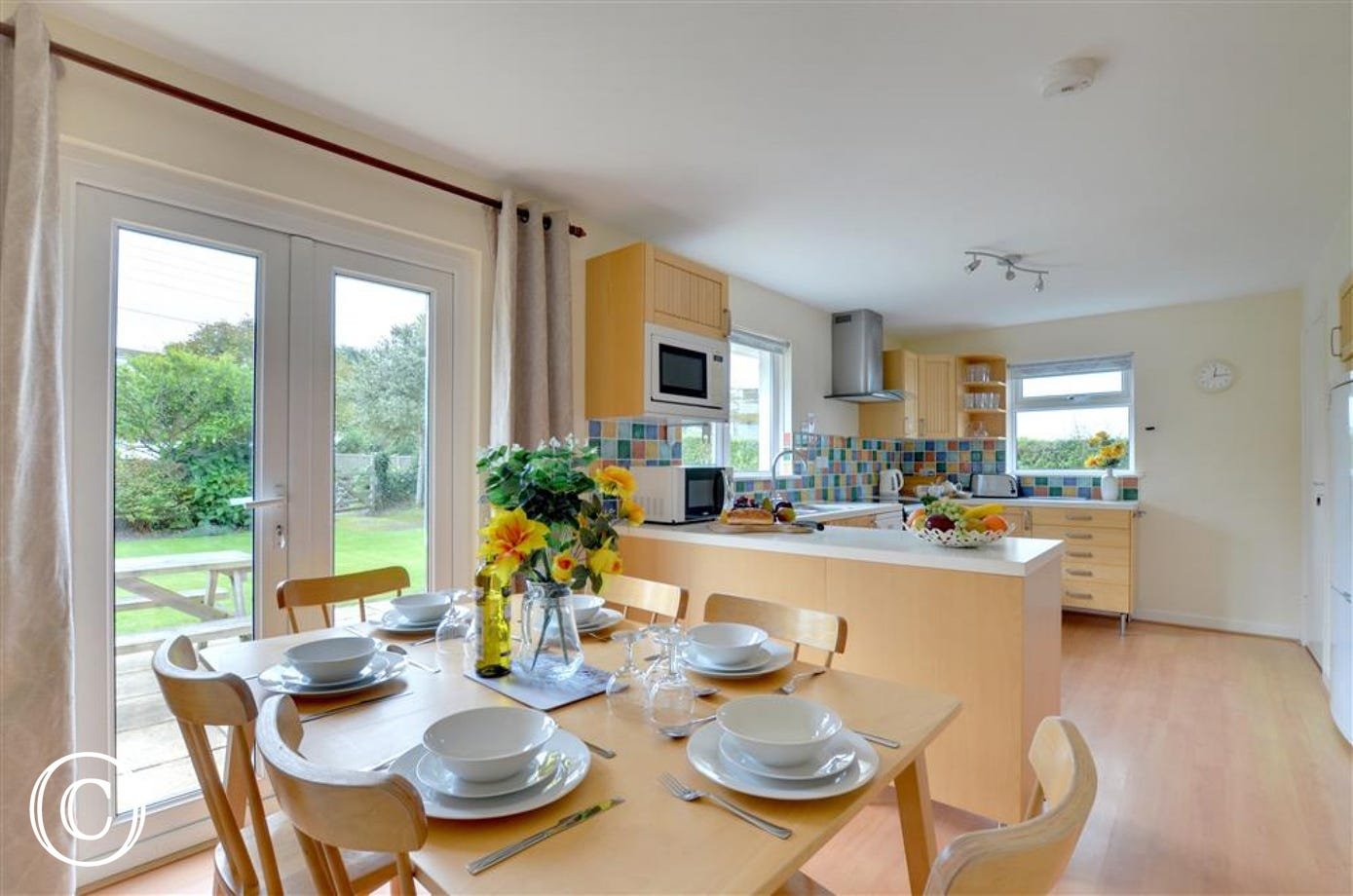 The spacious modern dining kitchen has patio doors out into the garden