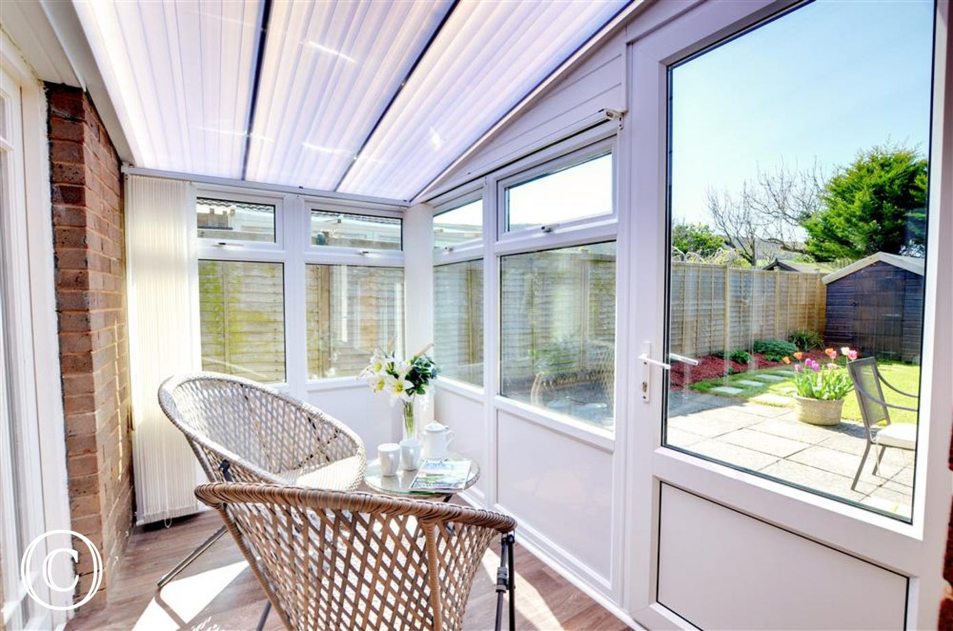 Small sun room with garden furniture which looks out onto the rear garden