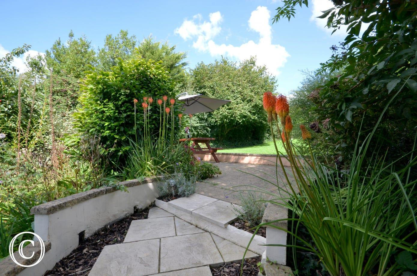 Steps lead up to the large enclosed garden with patio area, picnic bench and a good sized lawned area, ideal for children's play