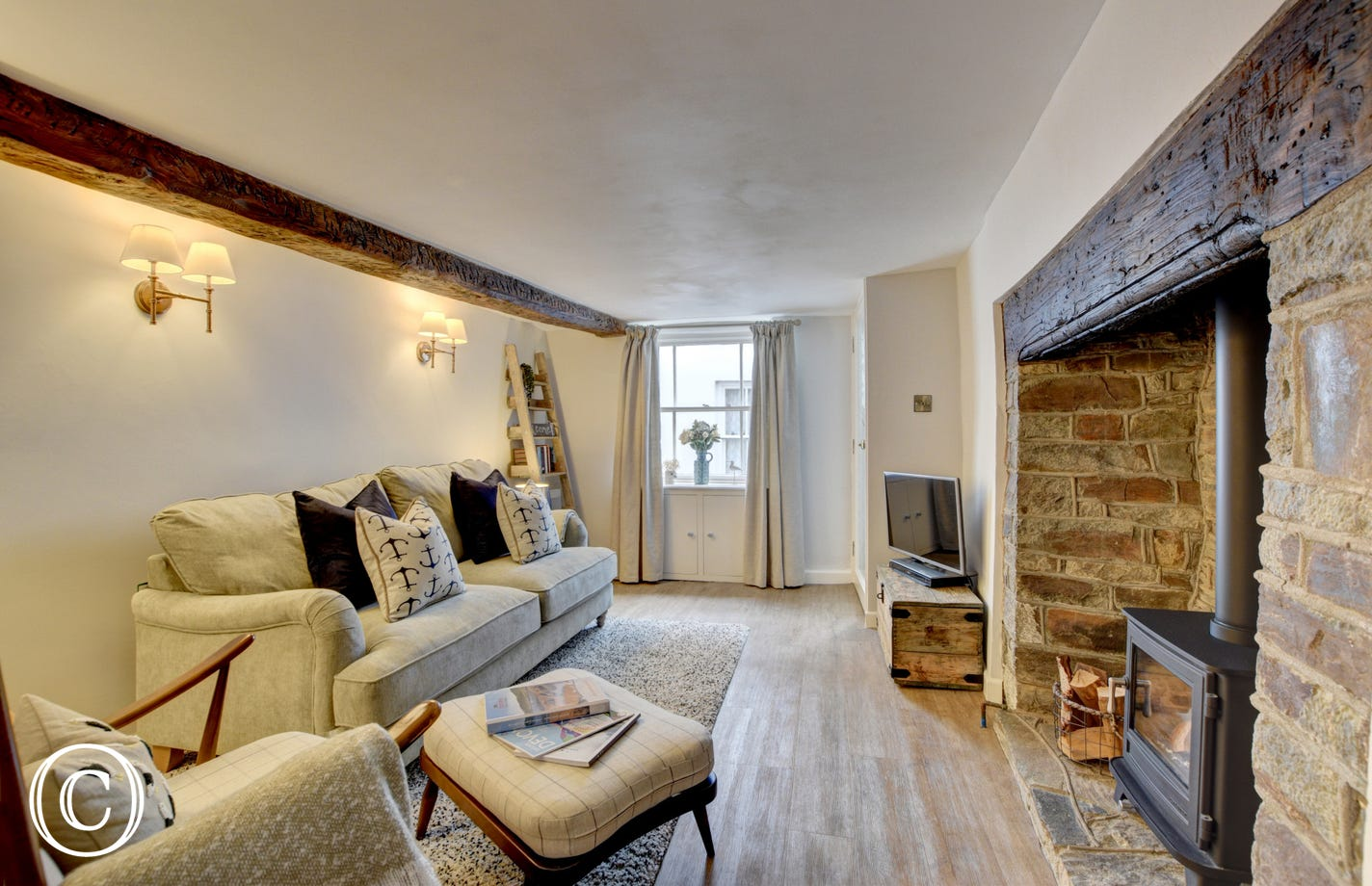 Attractive beamed living room with a woodburner in an inglenook providing a cosy focal point
