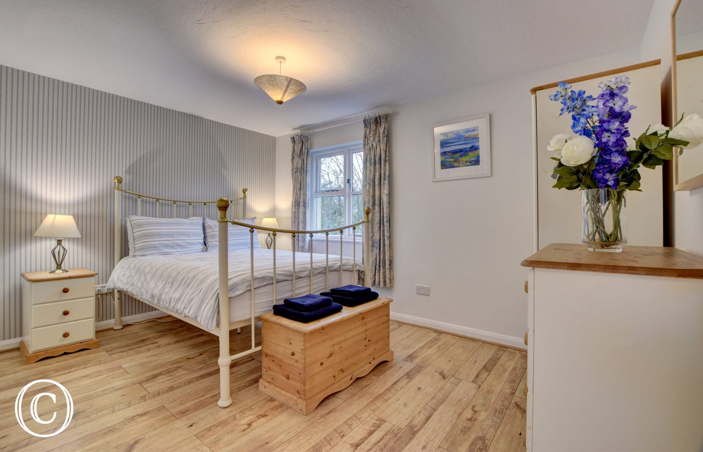 Comfortable and spacious master bedroom with garden views