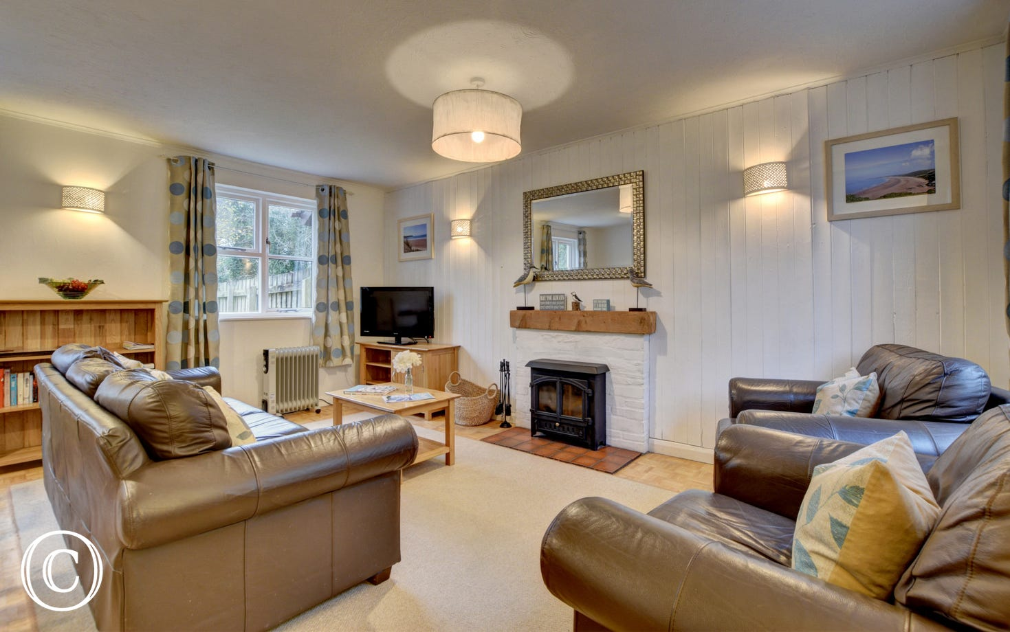 The stylish living /dining room has comfy leather sofas and a welcoming wood burning stove