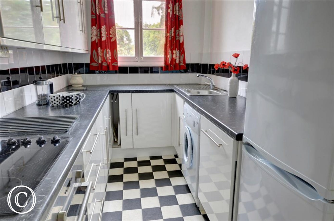 Smart white units and chequered flooring in the fully fitted kitchen