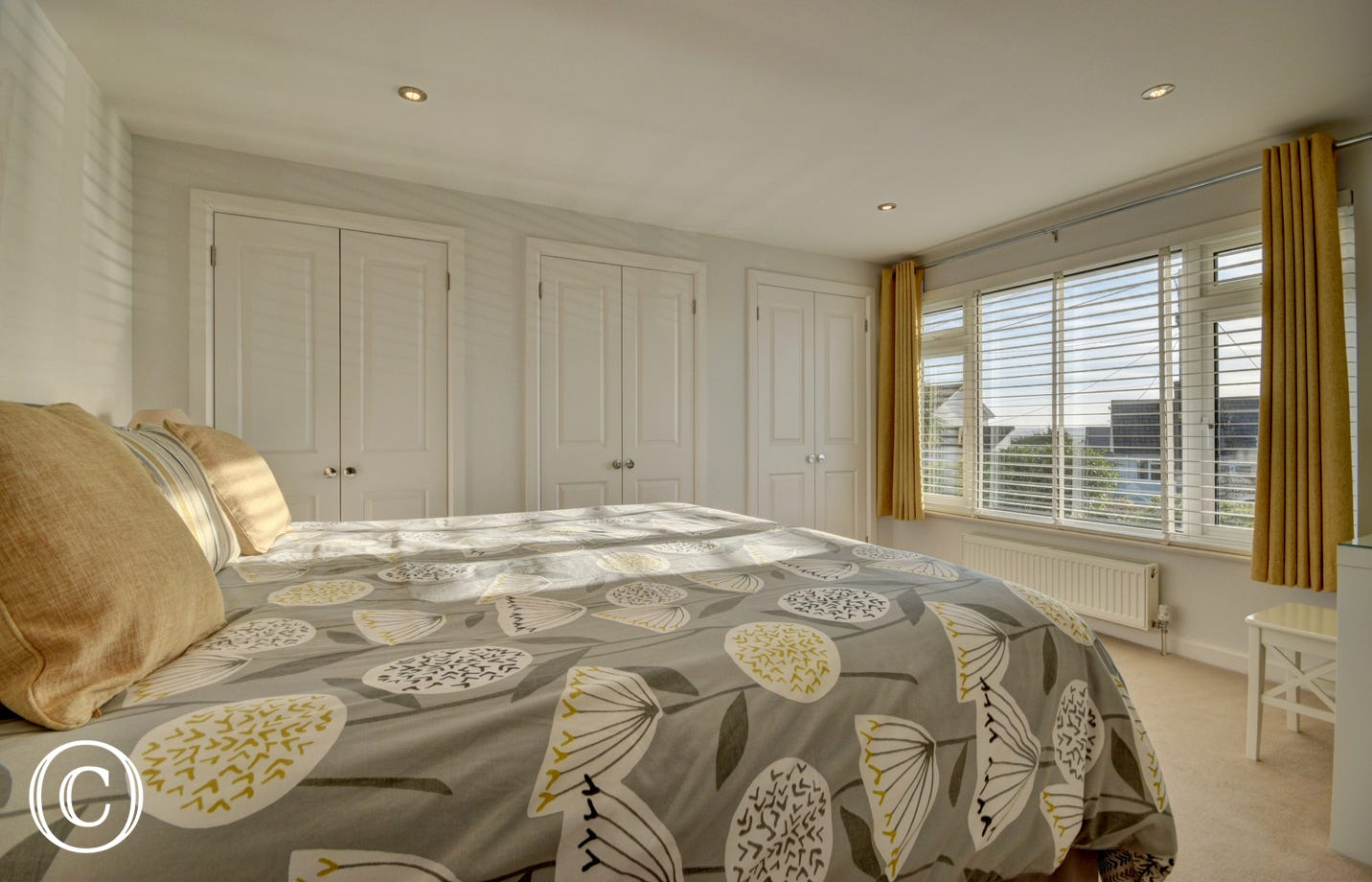 The master bedroom has two floor-to-ceiling built in wardrobes and large window with views over the front garden