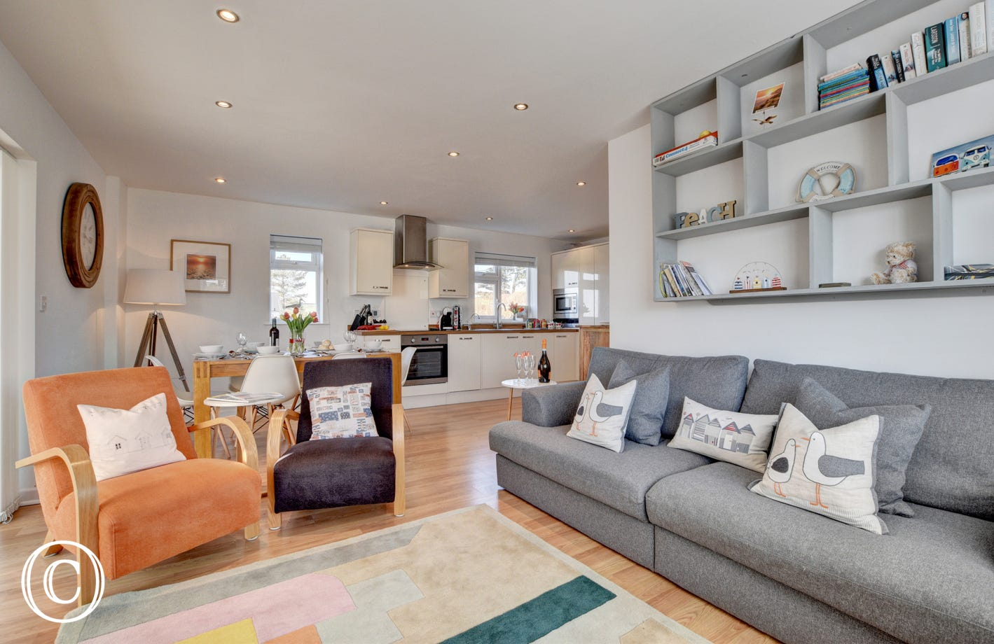 The main living area has a modern feel with comfy seating and the patio doors providing access to the garden