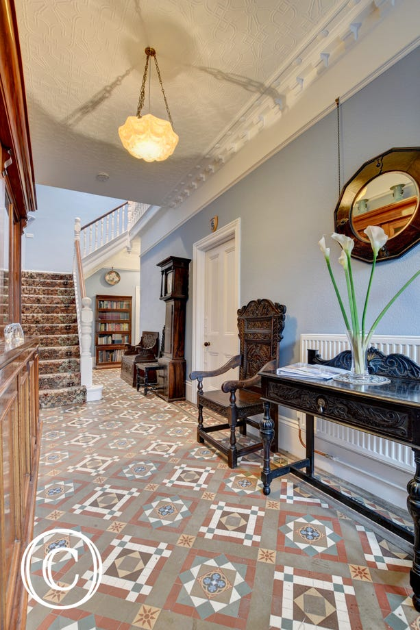 The entrance hall of the house has magnificent period floor tiles and part of the family collection of porcelain is on display