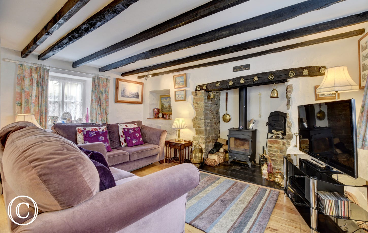 The sitting room has exposed beams and an inglenook fireplace