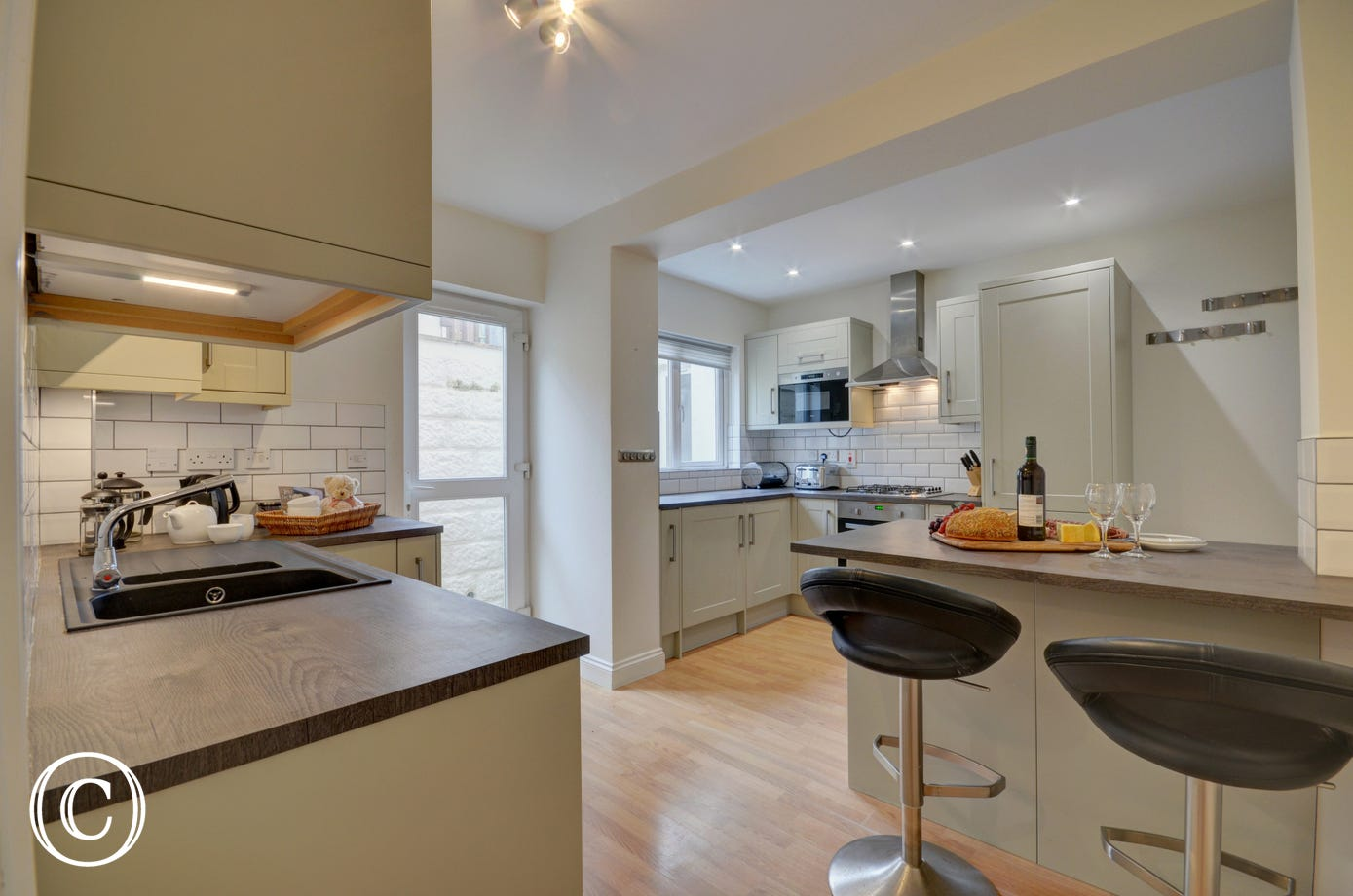 A separate, modern and well equipped kitchen with an additional small table for breakfast is to the rear