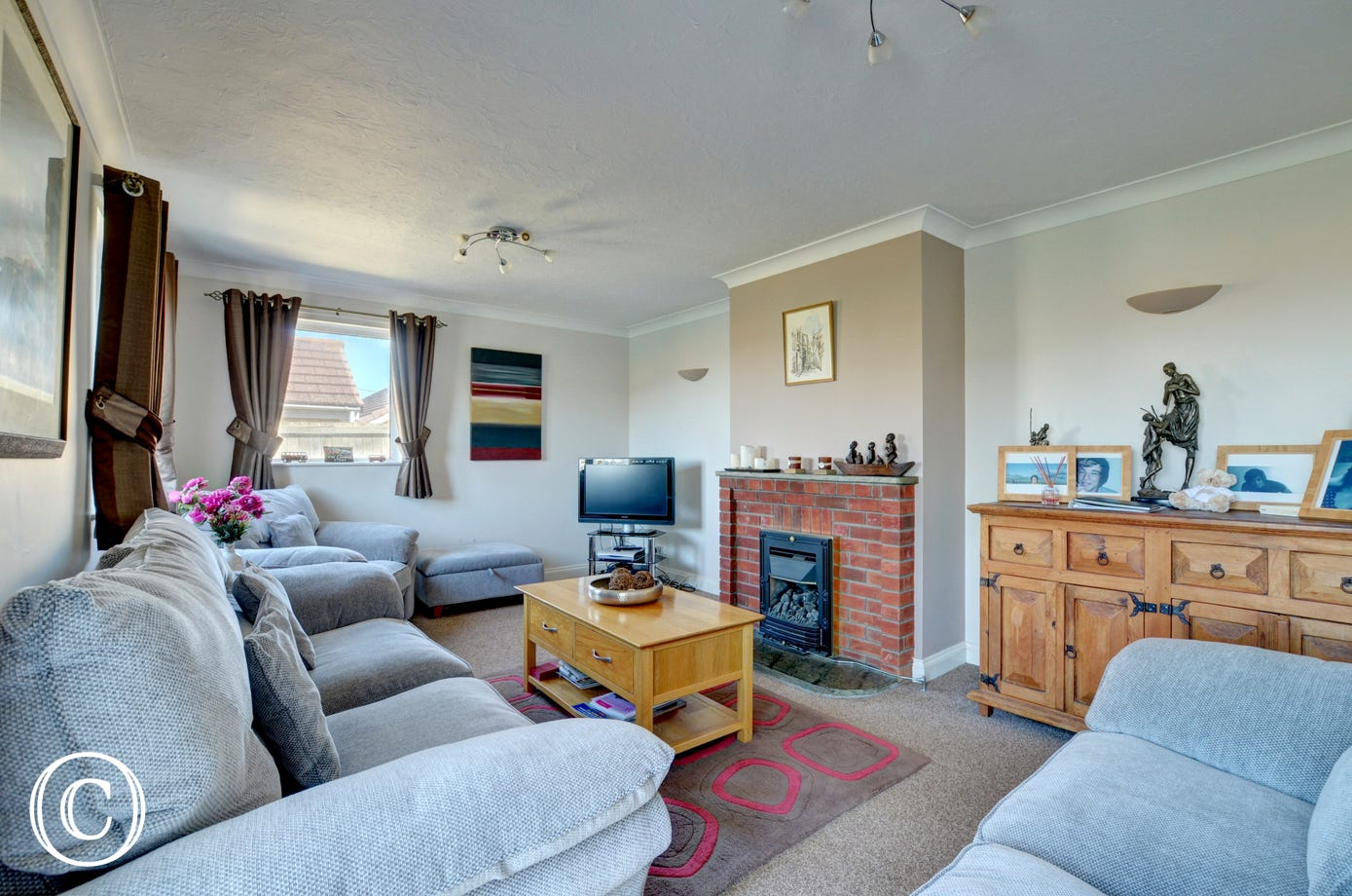 Comfortable sitting room with ample seating and cosy gas fire