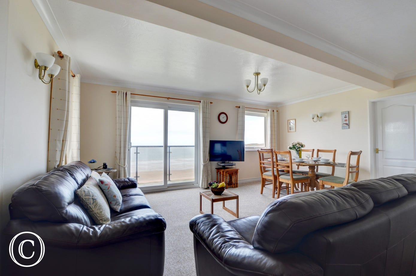 The spacious open plan living/kitchen area includes comfortable sofas and a dining area