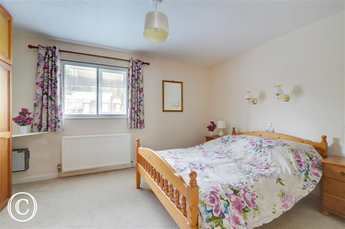 The spacious master bedroom looks over the garden