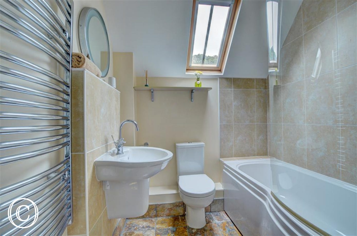 The contemporary bathroom has underfloor heating and a heated towel rail