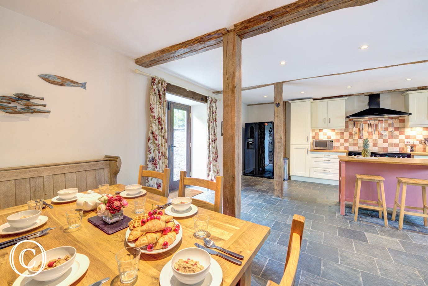 The kitchen is full of character with beams and a slate floor