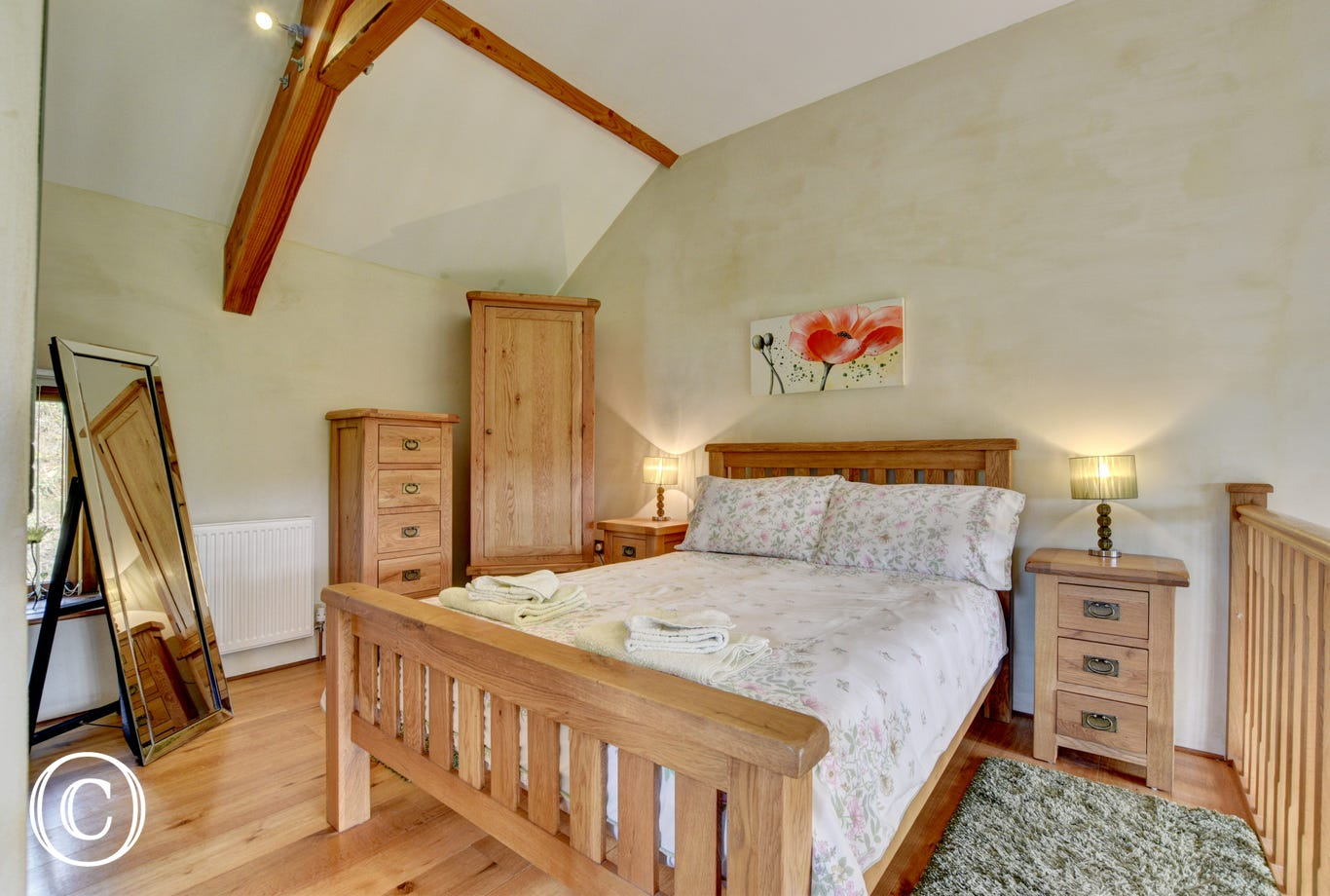 On a mezzanine floor above, the stylish bedroom has a pristine en suite shower room